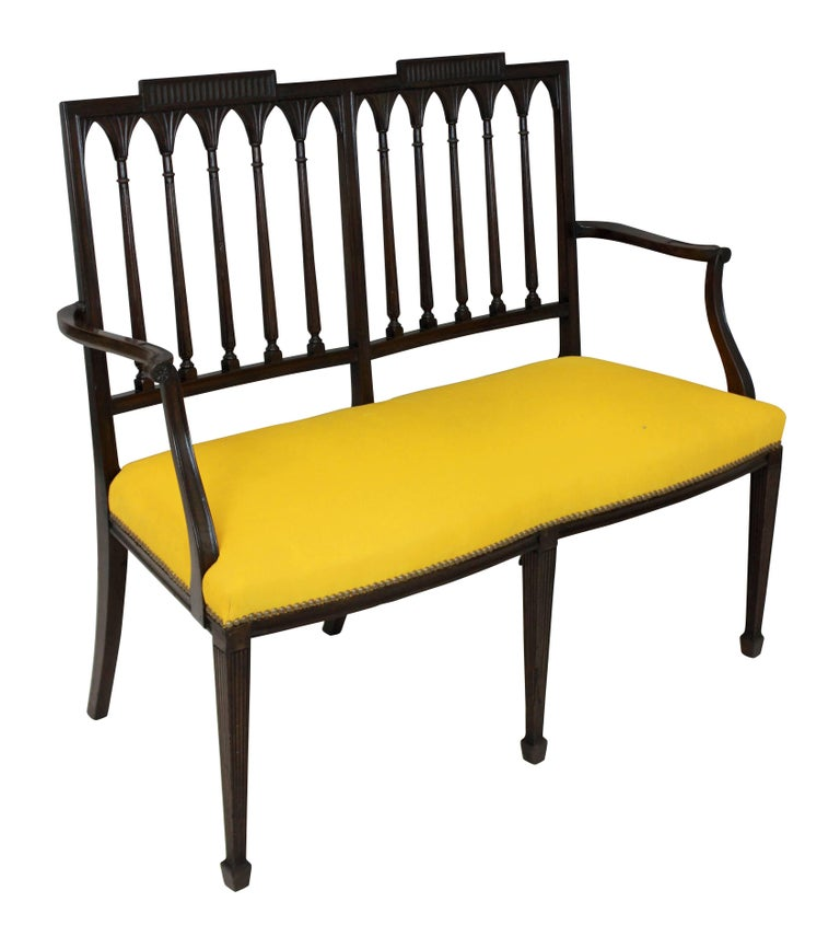 A mahogany Federal settee in the manner of Slover & Taylor of New York with a double tablet back, reeded spindles, legs and scrolling arms. Newly upholstered in canary yellow corduroy.