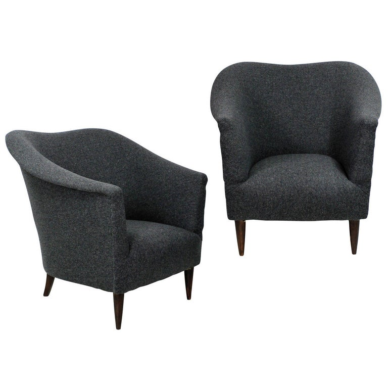 A pair of Italian sculptural armchairs with turned French polished feet and newly upholstered in grey wool.