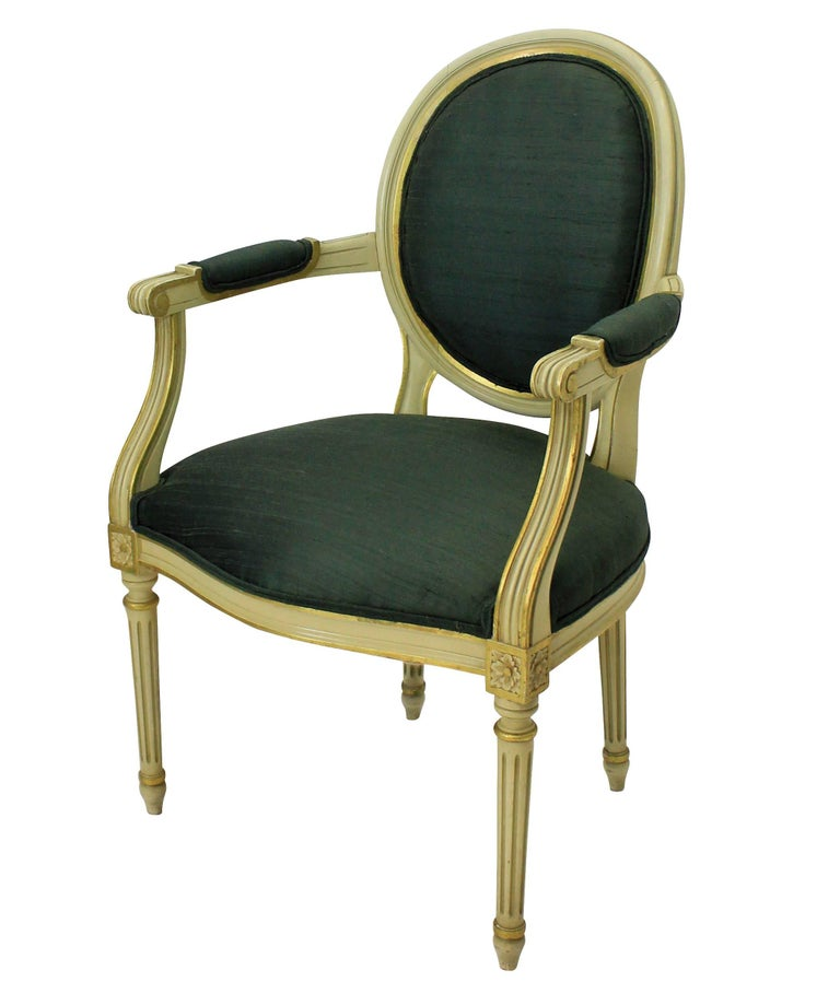 A pair of French painted and gilded Louis XV style armchairs upholstered in sage green silk.