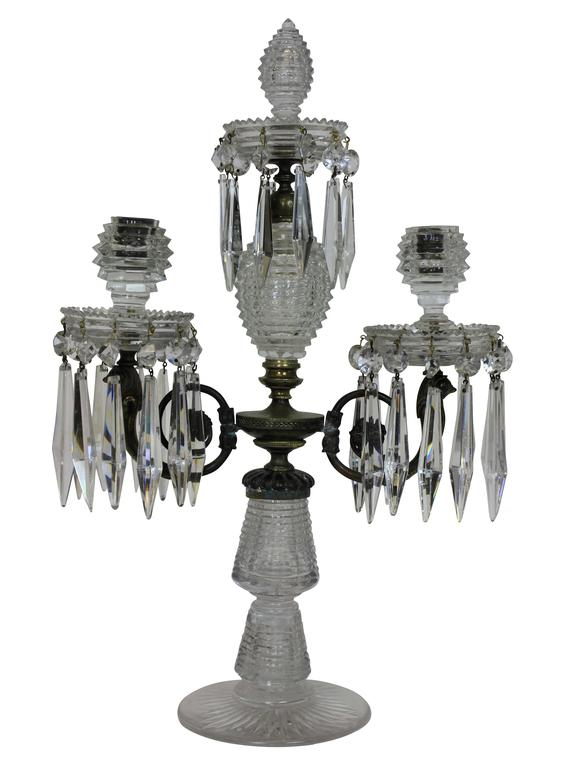 An English George III cut-glass and gilt bronze candelabra. Hand-cut in a 'bee hive' design, with twin branches and a central spike.
