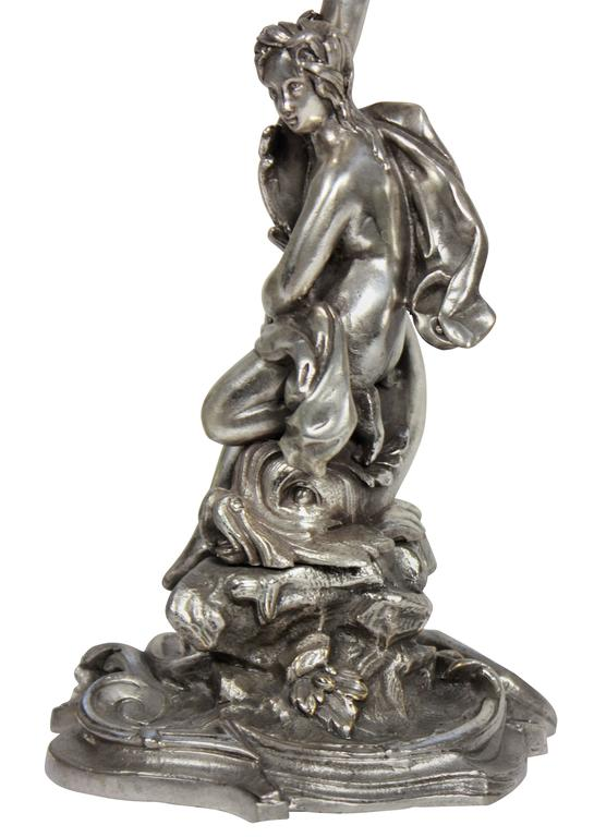 A pair of French silver plated bronze allegorical candlesticks with cut-glass drip pans, depicting male and female figures, riding on mythological creatures.