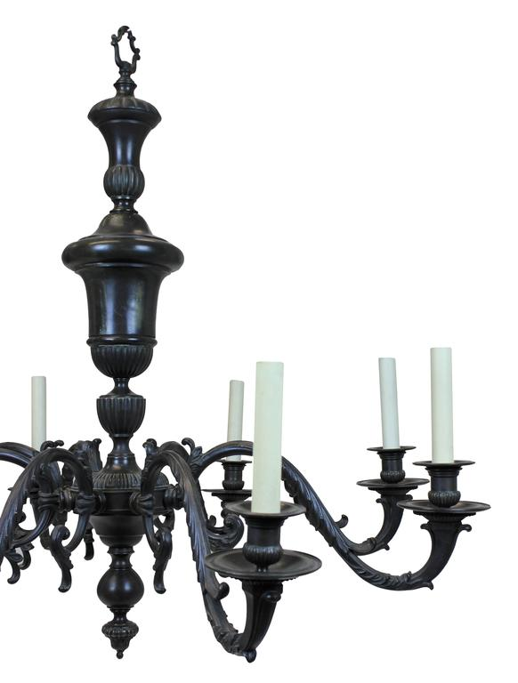 A large English 17th century style chandelier in bronze. With a Classical form, with baluster stem and eight large foliate arms with acanthus design.  Subjected to VAT.