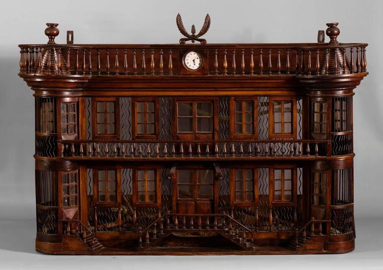 Superb and rare antique bird cage of the late 19th century made out of wood and metal representing a miniature castle adorned with a clock. It is a probable work of mastery: superb quality of the sculptures and refined details with balustrades,
