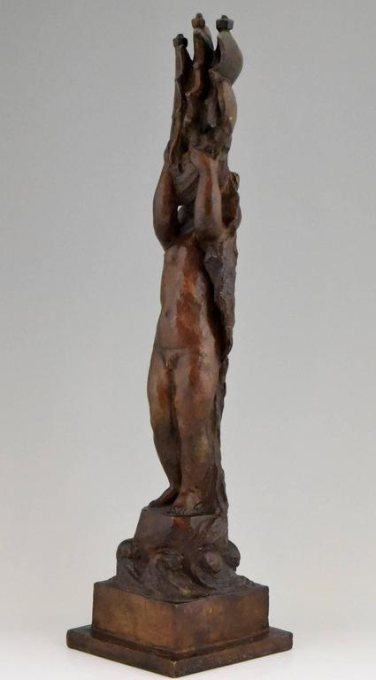 A typical Art Deco bronze modeled as a naked young boy wearing a hat, lifting a sailing boat high in the air. He is standing on a rock in the sea by the French artist Henri Raphael Moncassin, Foundry mark Susse Frère, lost wax technique.   Artist/