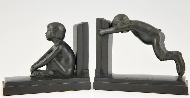 """""""Sit and push"""" Lovely pair of Art Deco styled figures on bookends representing male and female satyr.  Reduced version of the """"Miroir d'eau"""" fountains in Paris and Lucerne. Artist/ Maker: Paul Silvestre. Signature/ Marks: Silvestre,"""
