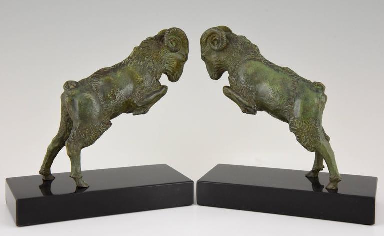 Art Deco bronze ram bookends. Signature/ marks: Scribe Style: Art Deco Date: 1930 Material: Bronze with green patina. Belgian black marble base. Origin: France Size: H 18 cm x L 17 cm x W 8 cm. H 7.1 inch x L 6.7 inch x W 3.1