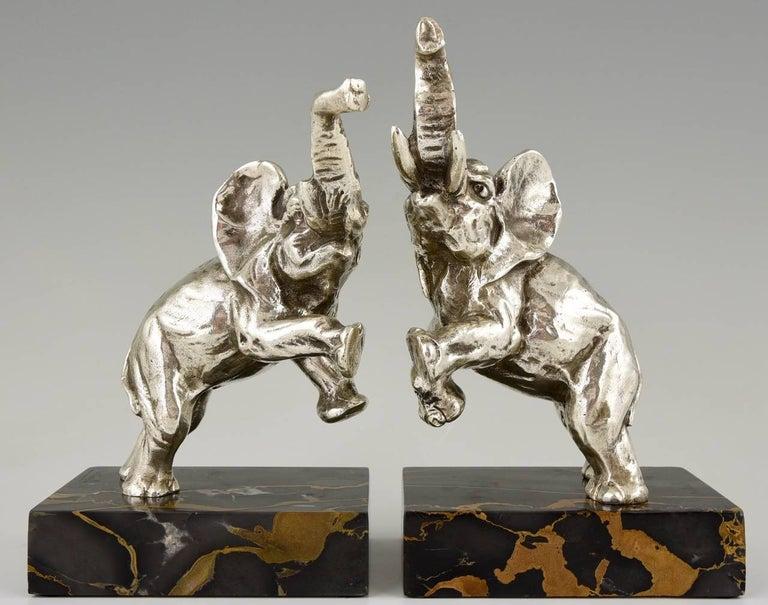 Description: Art Deco silvered bronze elephant bookends. Artist/ Maker: Jean de la Fontinelle. Signature/ Marks: L. Fontinelle.  Style: Art Deco.  Date: 1930.  Material: Silvered bronze. Portor marble base.  Origin: France.  Size of one:  H