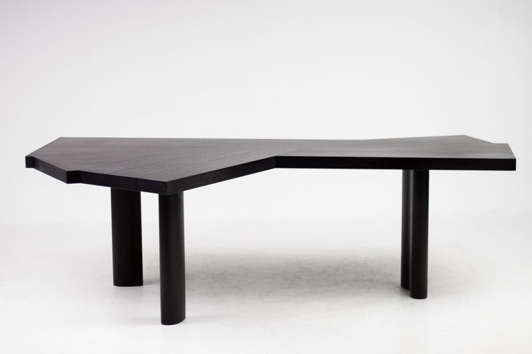 Table in black stained oak. The tabletop is composed of fourteen beams; the base has three legs.
