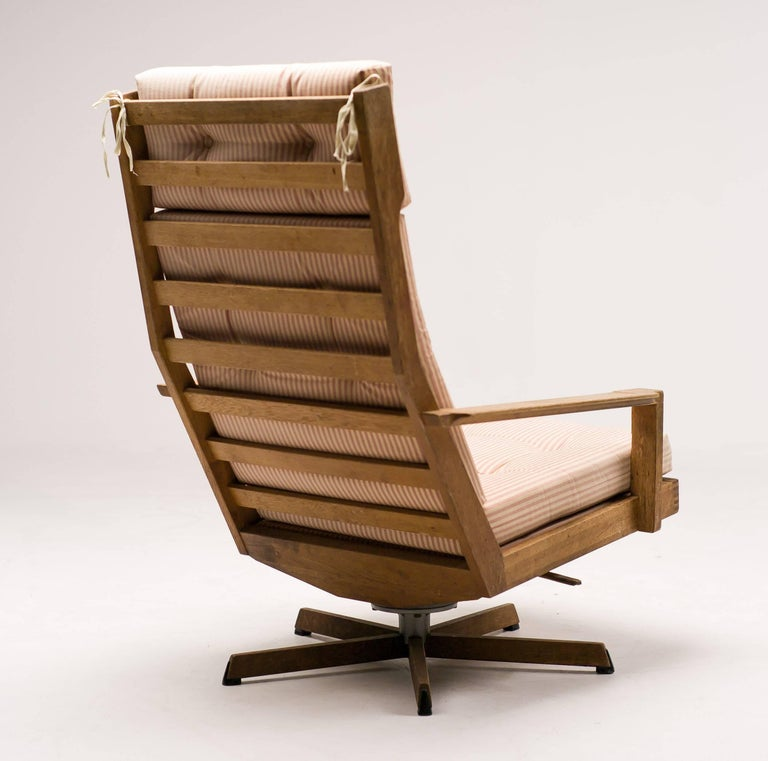 Scandinavian modern oak lounge chair with tilt/swivel and five-star oak base, manufactured by Madsen and Schubel. Beautiful construction with dovetail joints. Original striped cotton fabric in good condition.