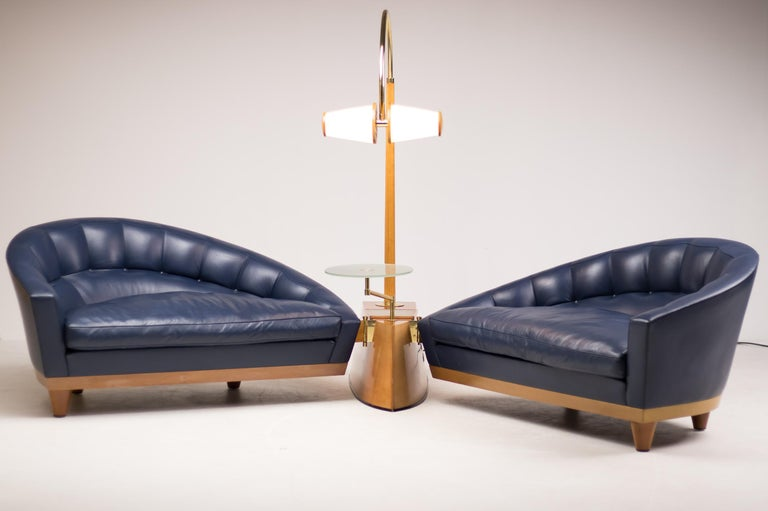 The centre of this piece is a heavy keel shaped base in solid cherrywood. The two blue leather sofas on solid cherry legs with concealed wheels are connected to the base by means of a polished brass hinge. The base also supports a cherry and brass