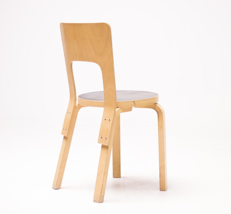 Alvar Aalto model 66 dining chairs manufactured by Artek, Finland. Birch plywood with black linoleum seat.  Made in 1980-2007, some marked with Artek label. Priced individually, circa 45 pieces available.