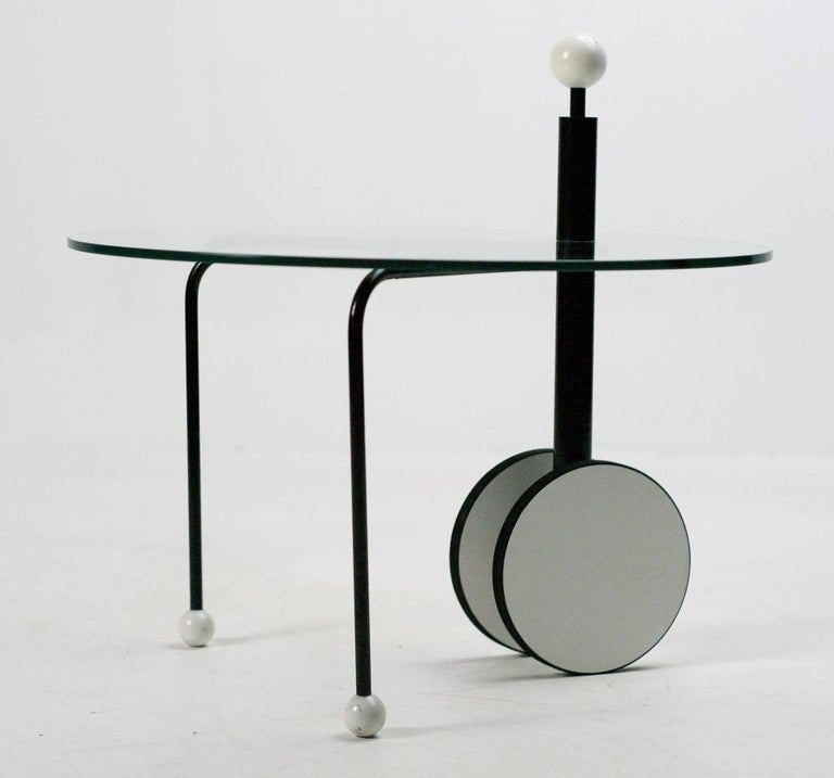 Side table designed by Alchimia and Memphis designer Michele De Lucchi. Clear glass tabletop with a rolling base. Lacquered wooden balls at the feet and on the upper grip.
