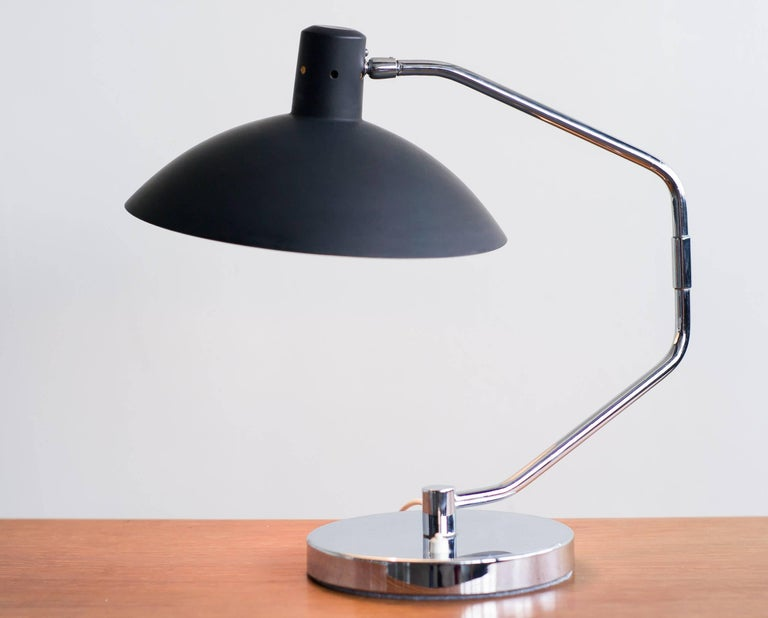 Iconic swing arm desk lamp model no. 8, designed by Clay Michie in 1958 and manufactured by Knoll International. Great vintage condition. The original black lacquer changed to a slightly dull charcoal color from age. The chrome base has a slight