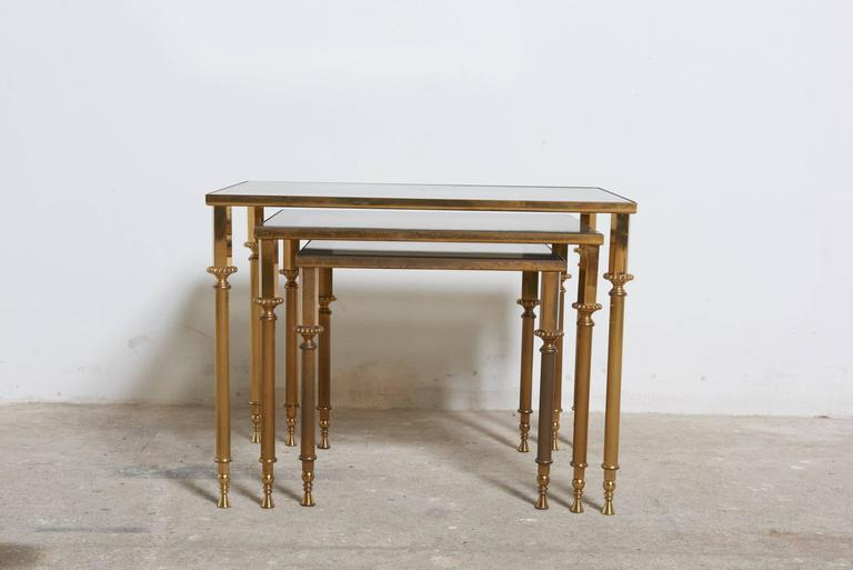 Set of vintage brass nesting tables in Neo-Classic design attributed to Maison Jansen with smoked, mirrored edge glass tops.