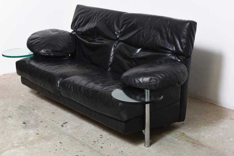 Arca two-seat, couch with right and left armrest provided with transparent glass serving tables which swing out from under the leather armrest.  Framework made of structural steel and black leather.  The backrests, which are easily adjustable,