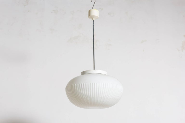 Beautiful opaline glass pendant with relief stripes that gives a very nice light effect in your office or living room, the suspension system is a chrome tube with a bakelite top. Eight pieces available. Free shipping worldwide.