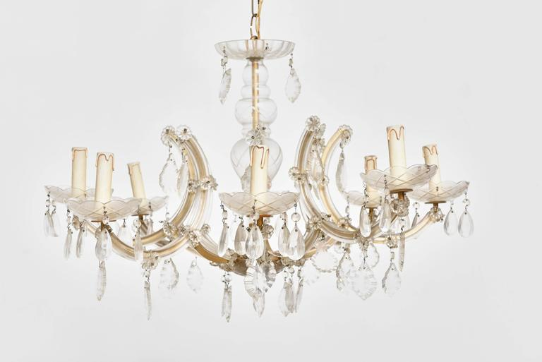 The Marie Therese 8 light chandelier has a flat metal frame but this is almost entirely covered in glass. Curved glass plaques or' listels' as they are known cover the arms. Glass drip bowls feature on every arm and the central column is also glass