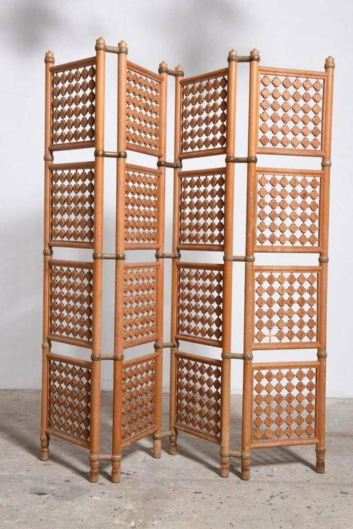 Beautiful walnut four-panel screen, room divider, framing with intricately carved geometric design medallions in wood and negative space.