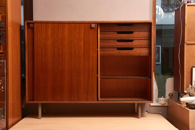 A 1960s Alfred Hendrickx Minimalist rosewood high sideboard.  Two sliding doors with metal square handles.  Inside three shelves and a compartment with four drawers and one shelve.   In excellent condition.