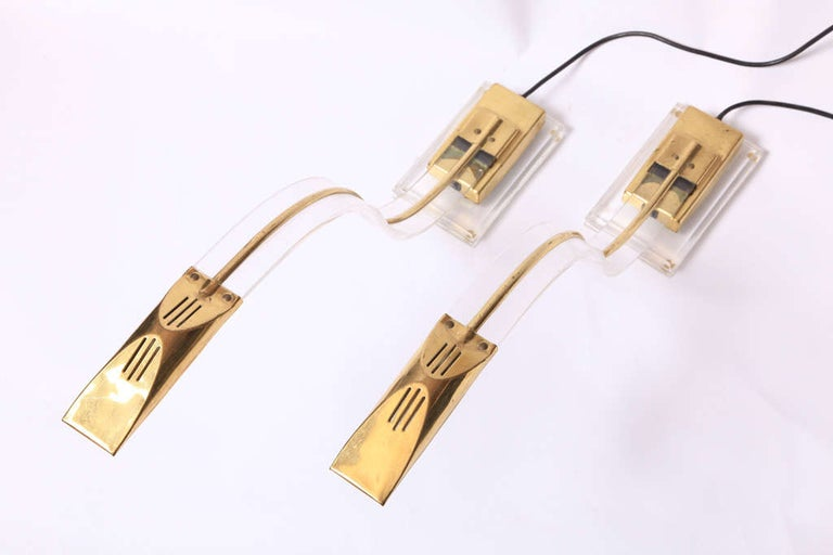 A set of two Lucite desk lamps with brass elements by Arredeluce, Italy, 1970s.   A beautiful set of desk lamps with reaching halogen light to read your paper or book through the reaching streamlined gooseneck, just one position.