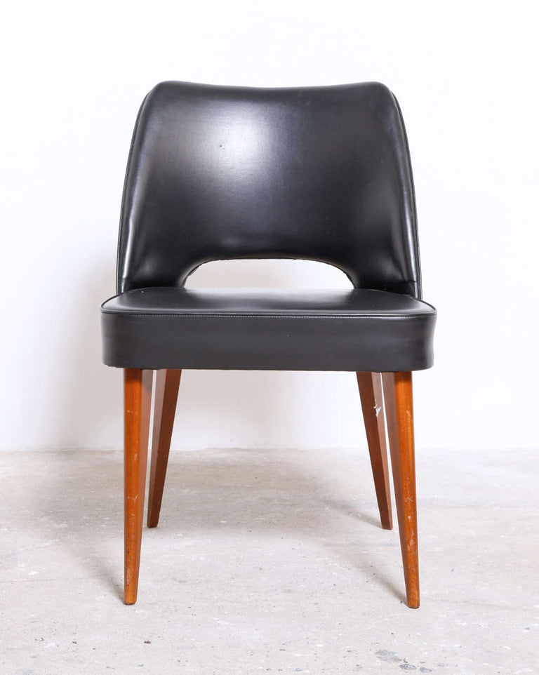 A set of four Mid-Century Modern organic form 1960s chairs with black leatherette upholstered and wooden legs made by Thonet. 