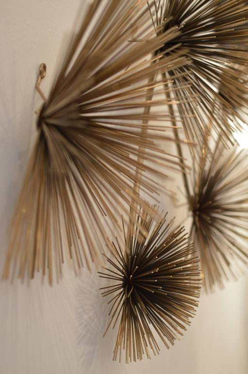 Metal 'Pom Pom' or 'Sea Urchin' wall sculpture executed in brass, fully signed and dated, 'C Jere 1979.' Sculpture can hang by one to three hooks in horizontal or vertical.