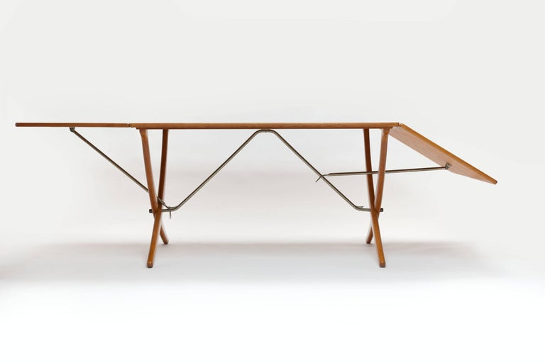 Hans J. Wegner oak dining table model AT-304 with two flip-down leaves and sabre cross-legs with brass stretchers, manufactured by Danish cabinetmaker Andreas Tuck (signed with burn mark). 