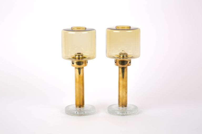 Hans Agne Jakobsson. A set of two brass candleholders with glass base by Hans-Agne Jakobsson for Markaryd, Sweden. The base is of glass with little air bubbles in it. String system for the candle.