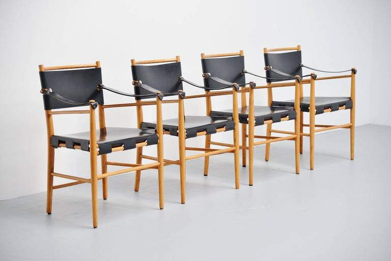 Very nice set of four highly decorative so called safari chairs made in Italy, 1960. These chairs have a solid birch wooden frame and thick black leather seat and back. The chairs are very nicely made and are very firm. The armrests of the chairs