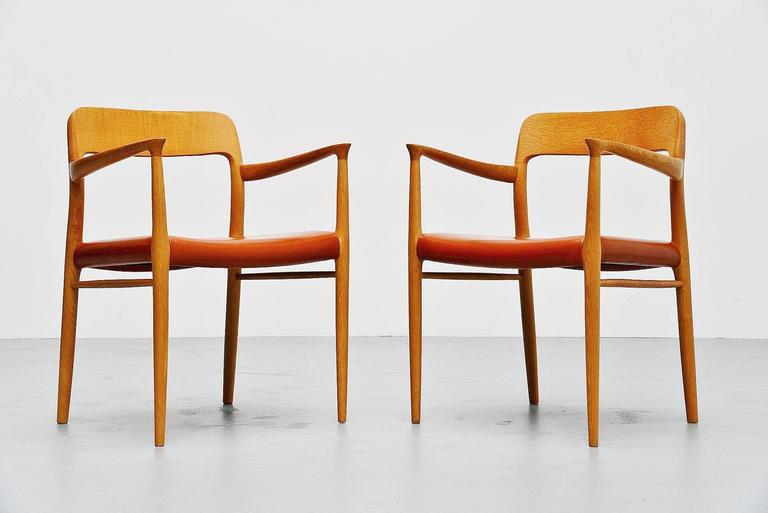 Very nice pair of arm chairs designed by Niels Otto Moller, manufactured by J.L. Møller Mobelfabrik, Denmark 1954. These chairs are made of solid oakwood and have very nice cognac leather upholstery. The chairs were hardly used by previous owner and