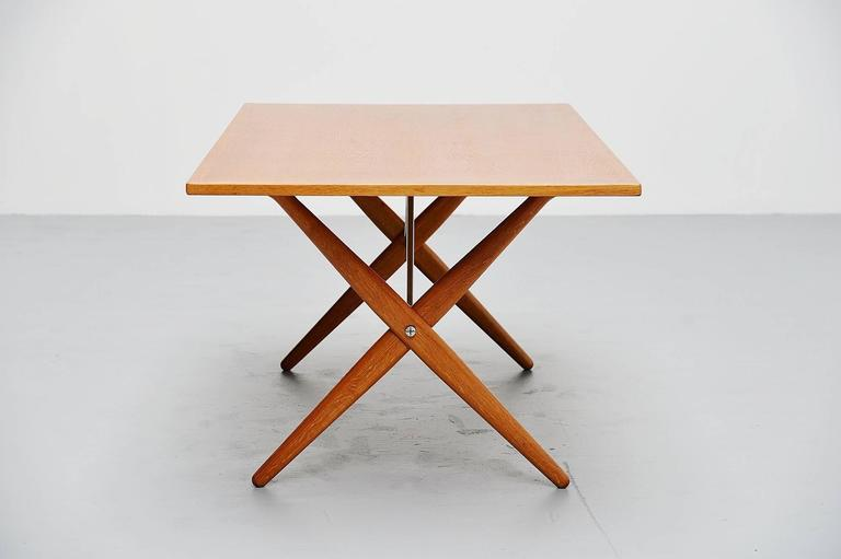 Iconic dining table mode AT-303 designed by Hans J. Wegner, manufactured by Andreas Tuck, Denmark, 1955. This table is made of solid oakwood and has very nice cross legged feet, supported with brushed steel tubular supports in the middle. The table