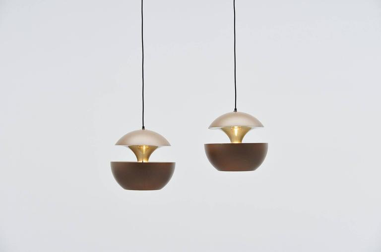 Large set of pendant lamps designed by Bertrand Balas and manufactured by RAAK Amsterdam, Holland 1970. These lamps are also called 'Springfontein' in Dutch, or fontaine jaillissante. The lamps have a brown painted shade and gold anodized inside for