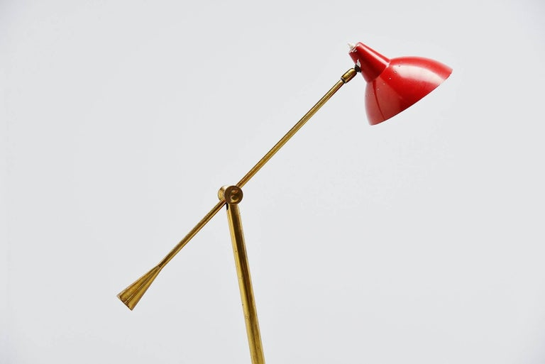 Very nice and typical Italian shaped floor lamp by Stilnovo, Italy, 1950. The base has a round brown marble base and a brass arm with weight for the balance. The shade is originally red painted. This lamp can be used as a reading lamp easily and
