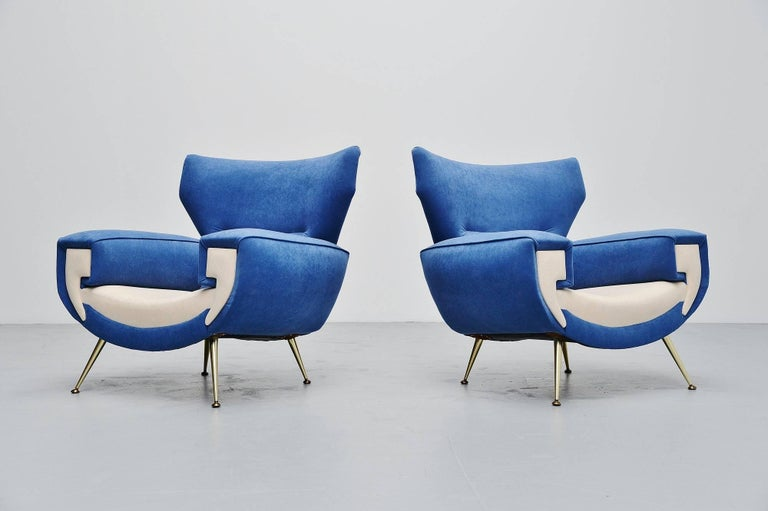 Spectacular pair of large club chairs made by unknown manufacturer or designed, Italy 1960. These nice shaped chairs have brass legs and we have newly upholstered them in blue and white velvet fabric upholstery. The chairs have a very nice and