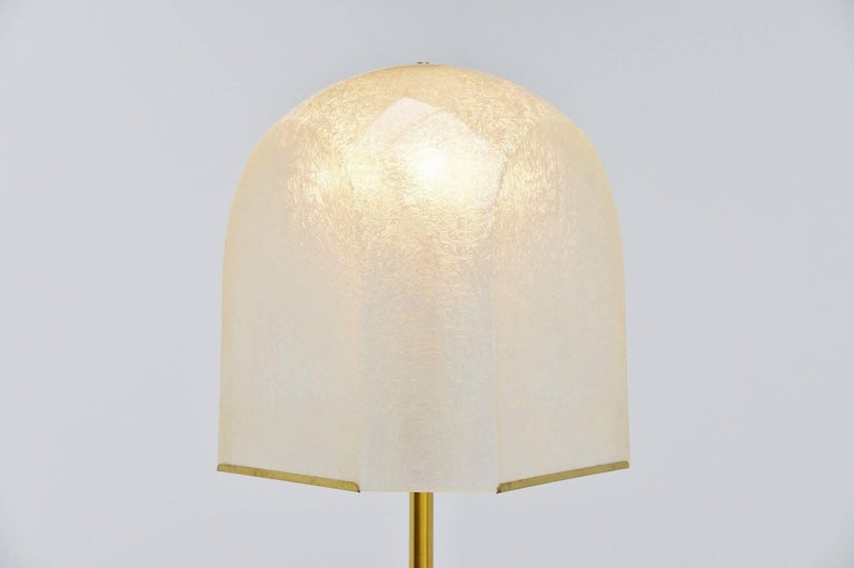 Large impressive floor lamp designed by Salvatore Gregorietti and manufactured by Lamperti, Italy 1960. This lamp has a nice fiberglass shade and a brass stem with a weighted travertine base. The lamp gives very nice and warm light when lit and uses
