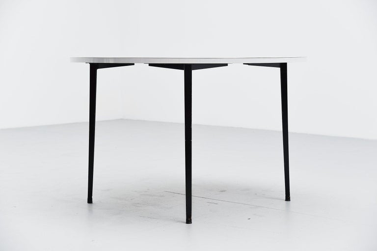 Rare round dining or working table designed by Friso Kramer for Ahrend de Cirkel, Holland, 1955. This table has a very nice light grey formica top and four black metal legs. This table has normal user wear along on the legs fits the industrial style