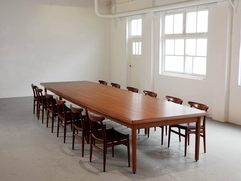 Conference table, teak, Denmark, 1960s.   Very large dining table in teak. This table consist of a large boat shaped top with eight cubic legs. The top is nicely detailed with a teak frame. Due the large size the top is a great surface to show the