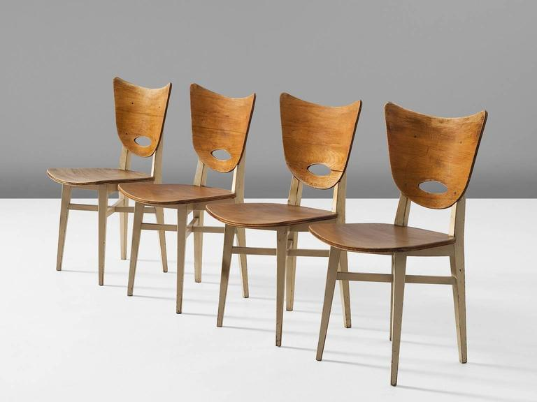Set of four chairs, in beech, Europe, 1950s.   Set of four dining chairs in stained beech. These chairs show nice organic lines in the back and seating, accompanied by a traditional frame. The white lacquered frame makes a nice contrast to the brown