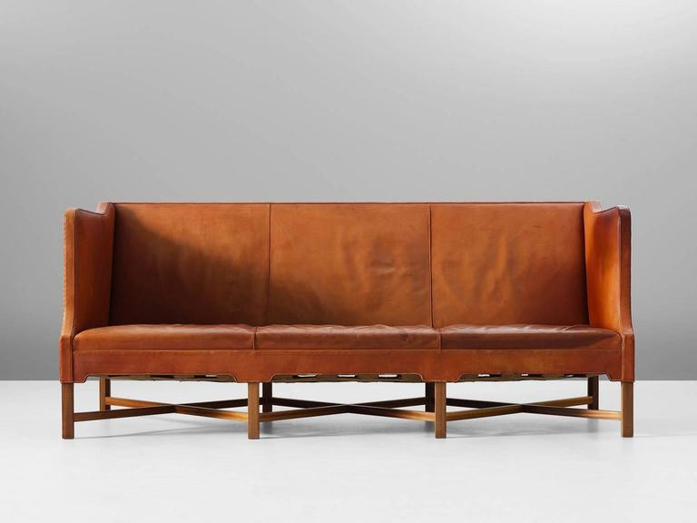 Kaare Klint for Rud Rasmussen, sofa model 4118, in leather and mahogany, by Denmark 1929.  Classic and elegant Scandinavian three-seat sofa by Kaare Klint. This model was designed in 1929. The base consist of eight legs in mahogany with X-shaped