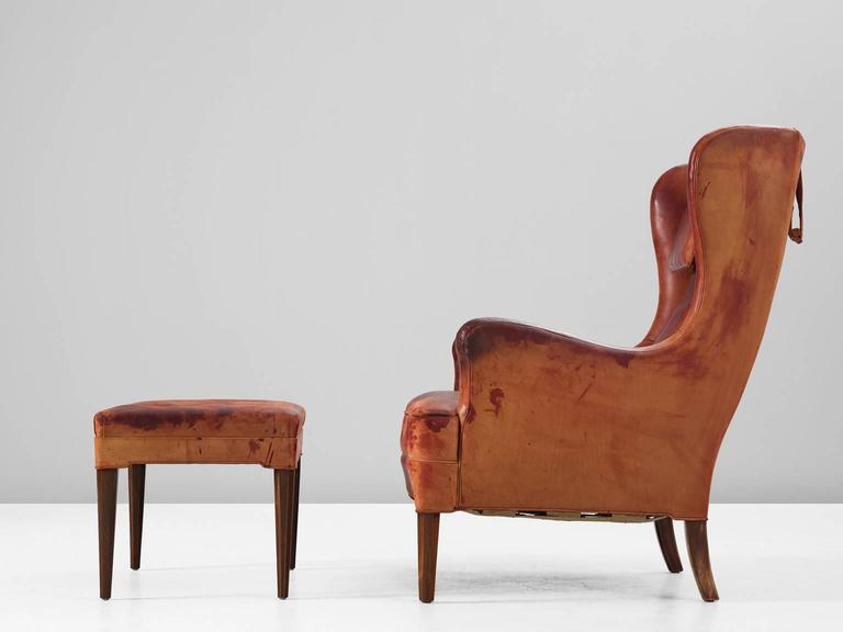 Scandinavian Modern Frits Henningsen Wingback Chair and Ottoman in Original Cognac Leather For Sale
