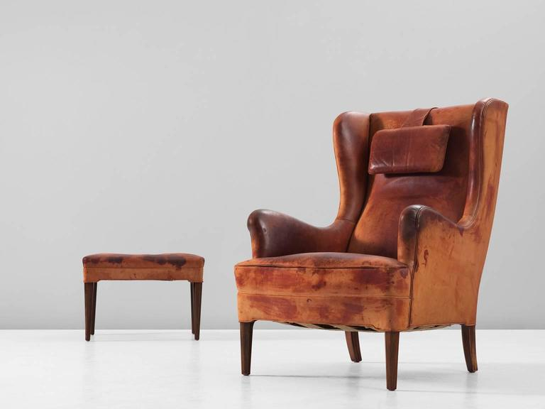 Wingback chair and ottoman in leather and wood by Frits Henningsen, Denmark, 1940s.