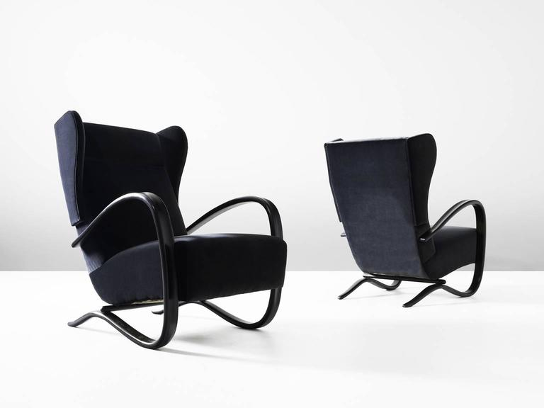 Pair of armchairs, in beech and fabric, by Jindrich Halabala, Czech Republic, 1930s.   These lounge chairs have a very dynamic appearance, due the curved base that ends fluently in the armrests. The dark brown stained wood nicely blends with the