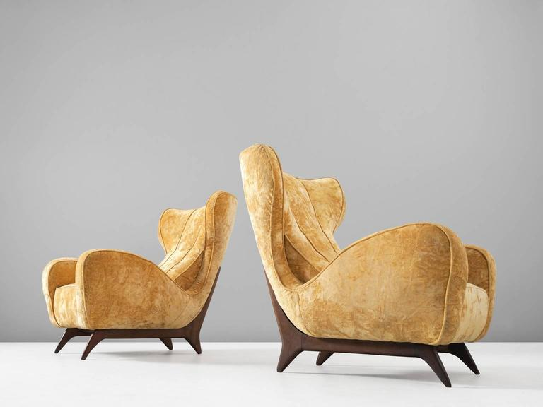 Pair of lounge chairs, in fabric and wood, attributed to Carlo Graffi, Italy, 1950s.   Set of two large and comfortable lounge chairs. These reupholstered chairs have a very present character. The back is high with characteristic 'wings,' which run