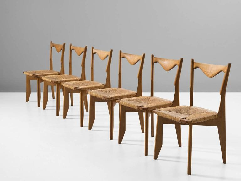 Set of six dining chairs, in oak and papercord, by Guillerme & Chambron, France, 1960s.  Set of six elegant dining chairs in solid oak by Guillerme and Chambron. These chairs show the characteristic frame of this French designer duo. Tapered
