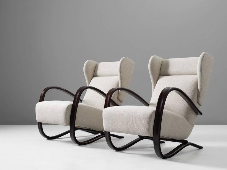 Jindrich Halabala, pair of armchairs, in stained beech and fabric, by  Czech Republic, 1930s.   This Halabala chairs are part of the Morentz midcentury design collection. These lounge chairs have a very dynamic appearance, due the curved base that