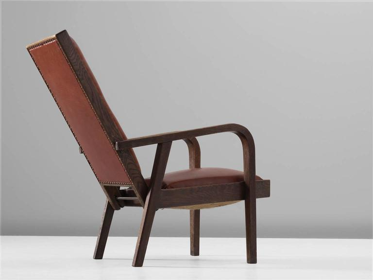 Adjustable armchair in red leather and oak, 1930s, Europe.  This adjustable chair is architectural in its design as it can define a space even though it is an individual object. The straight back is both elegant and sturdy. The curved armrests are