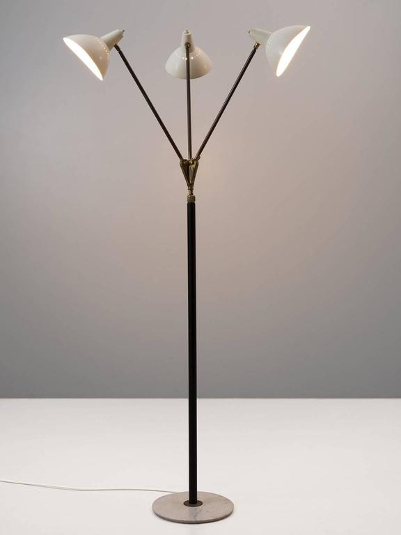 Floor lamp, in brass, metal and marble, for Stilnovo, Italy, 1950s.  Stunning floor lamp with three white coated shades in all directions and can be switched of separately. Each shade is supported by a brass stern, which combine into one black