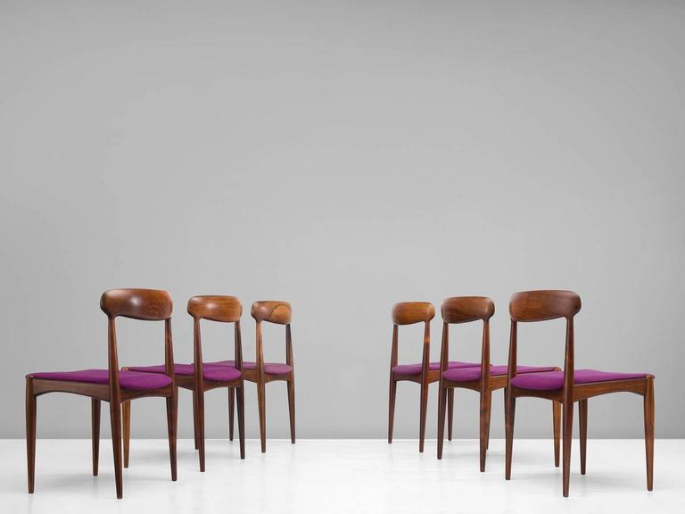 Dining room chairs, rosewood, purple fabric by Johannes Andersen and manufactured Uldum furniture factory, Denmark,1960s.  The restrained chic rosewood dining chairs are soft and warm in their appearance. The backrest is slightly tilted and