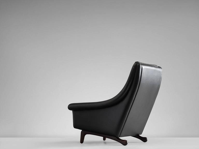 Easy chair, black leather and wood, Denmark, 1960s.  This organically shaped armchair features an organic base that is sculptural and crafted in an exquisite manner. The stained legs form a great combination with the fluent curved shaped of the