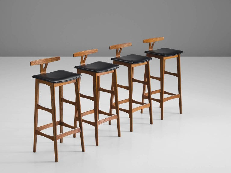 Four bar stools, teak and black leather designed by Knud Bent for Dyrlund, Denmark, 1950s   This unusual set by Knud Bent features a solid teak frame with leather seat. The most distinct feature of this unique design is the low T-shaped backrest
